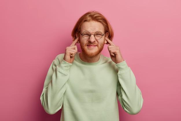 Przystojny młody rudowłosy facet ma rudą brodę i przeszkadza mu dokuczliwy hałas
