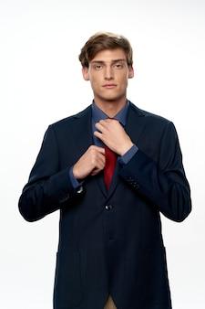 Przystojny młody samiec model w eleganckim kostiumu pozuje w studiu