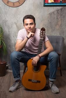 Przystojny młody siedzi na krześle i trzyma gitarę.