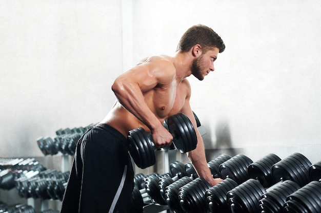 Przystojny młody sportowiec ćwiczący na siłowni