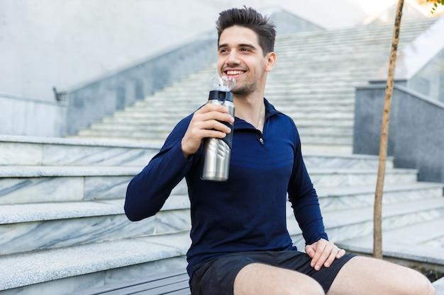 Przystojny młody sportowiec pije wodę z butelki na zewnątrz, siedząc na schodach