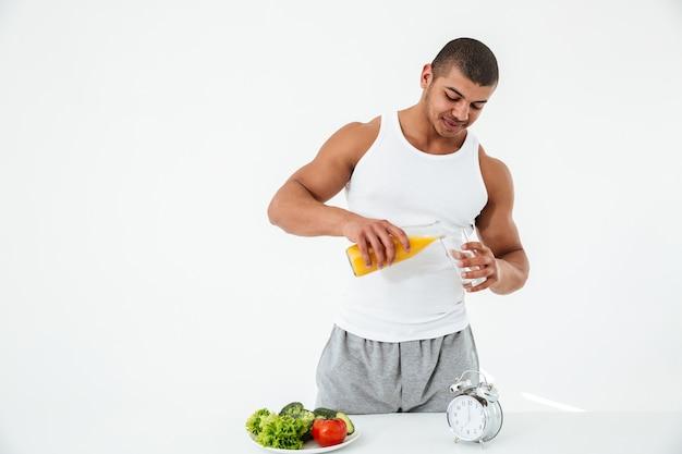 Przystojny młody sportowiec trzyma szklankę soku.