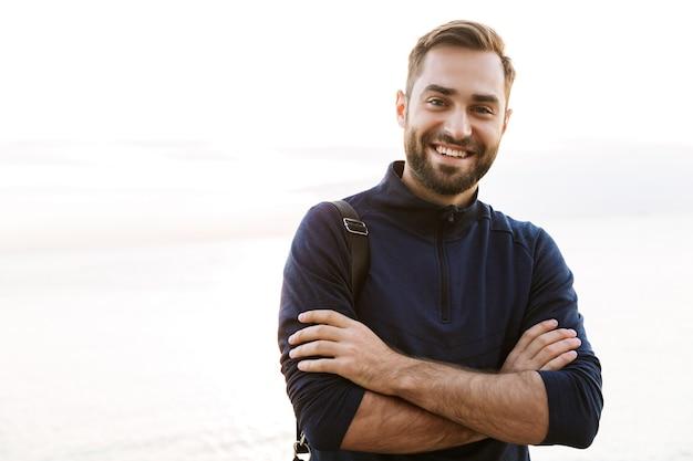 Przystojny młody sportowiec w torbie stojącej na zewnątrz, z założonymi rękami