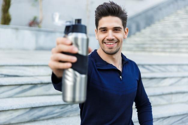 Przystojny młody sportowiec wody pitnej z butelki na zewnątrz