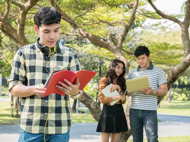 Przystojny młody student collegu mienia książki i ono uśmiecha się