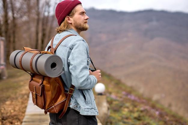 Przystojny młody stylowy mężczyzna w dżinsowej kurtce z plecakiem, spacery w przyrodzie.