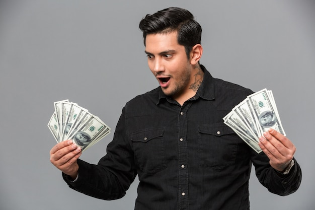 Przystojny młody szokujący mężczyzna trzyma pieniądze.