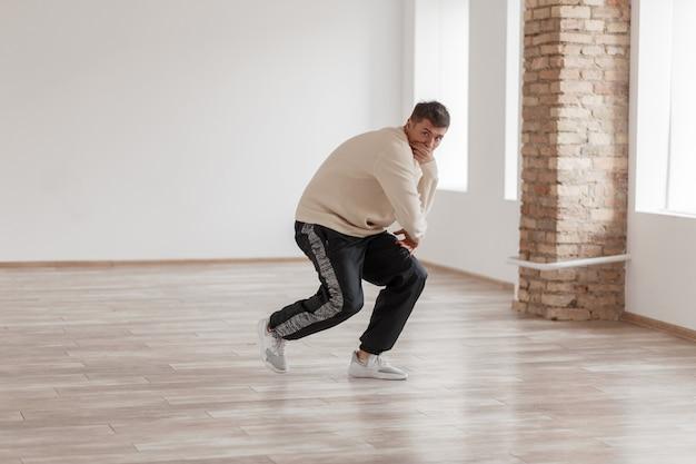 Przystojny młody tancerz hip-hopu tańczy ukrywając twarz w biały sweter i czarne spodnie w studio tańca