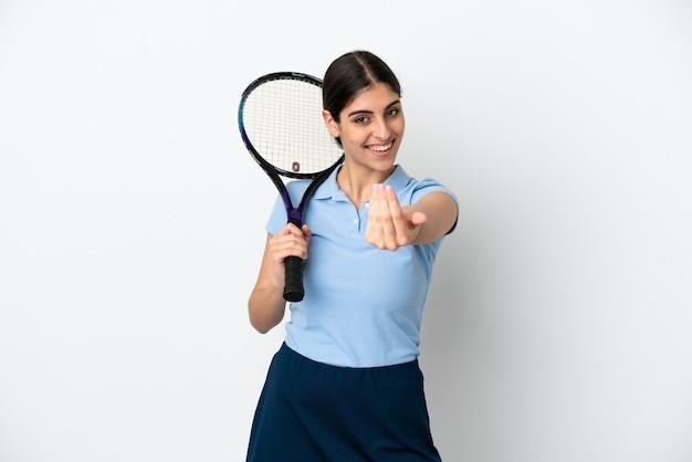 Przystojny młody tenisista kaukaski kobieta na białym tle zapraszając przyjść z ręką. cieszę się, że przyszedłeś