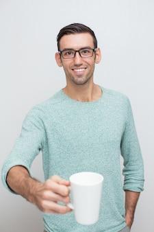 Przystojny młody uśmiechnięta człowiek oferuje kubek herbaty