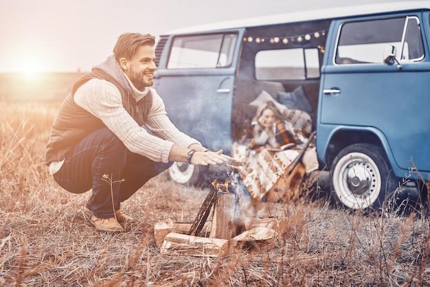 Przystojny młody uśmiechnięty mężczyzna siedzi przy ognisku, podczas gdy jego dziewczyna relaksuje się w retro minivanie