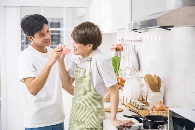 Przystojny młody wesoły karmienie szynką swojego partnera lgbt w kuchni podczas gotowania posiłku. urocza homoseksualna rodzina tej samej płci w weekend.