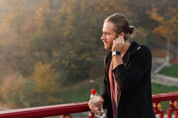 Przystojny młody wysportowany sportowiec słuchający muzyki za pomocą bezprzewodowych słuchawek na moście, trzymający butelkę wody