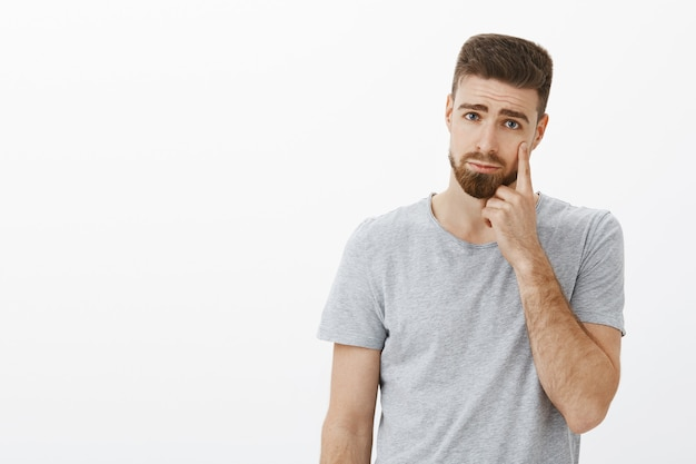 Przystojny młody, wzruszony facet z brodą robi smutny i ponury wyraz twarzy, wskazując na powiekę, jakby pokazywał łzę wyrażającą żal lub smutek stojący niezadowolony, płaczący nad szarą ścianą