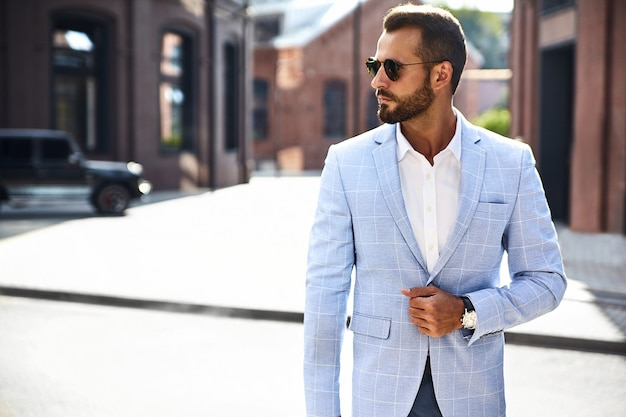 Przystojny moda biznesmen model ubrany w elegancki niebieski garnitur pozowanie na ulicy