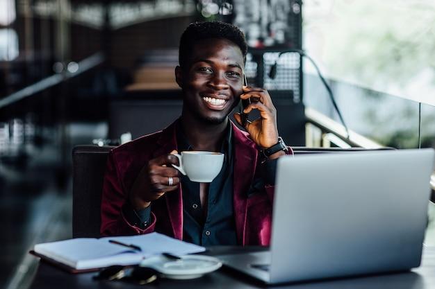 Przystojny model, afrykański młody mężczyzna pracujący na komputerze przenośnym na tarasie w kawiarni w europejskim mieście.