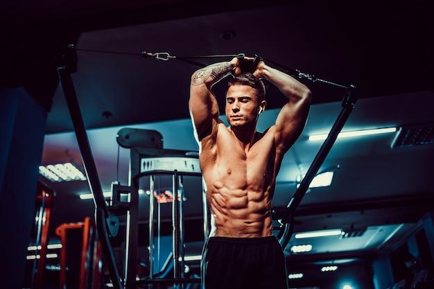 Przystojny model fitness bez koszuli w siłowni treningu sześciopak w maszynie do chrupania. bliska koncepcja abs. styl życia opieki zdrowotnej