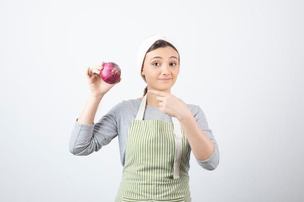 Przystojny model kobiety w fartuch, wskazując na fioletową cebulę.