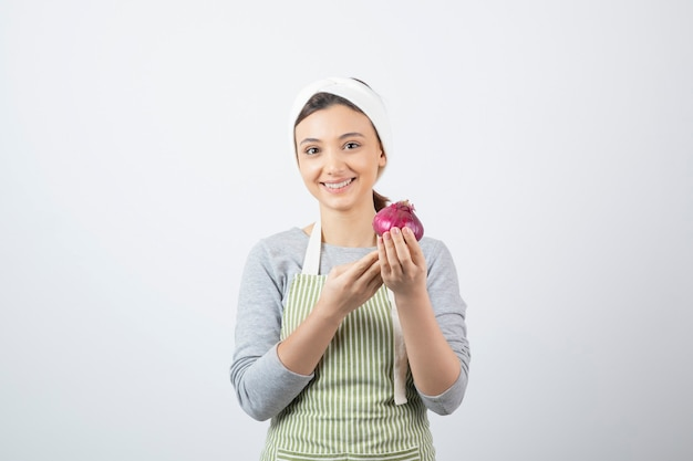Przystojny model kobiety w fartuchu trzymając fioletową cebulę.