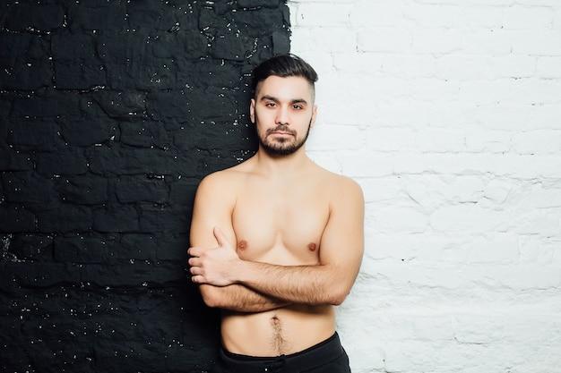 Przystojny model mężczyzna pozuje na białym tle na białej i czarnej ścianie