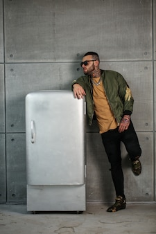 Przystojny model mężczyzna z modnym tatuażem i czarną brodą stojącą i pozującą w pobliżu stylowej starej lodówki retro zsrr w modnych ubraniach.