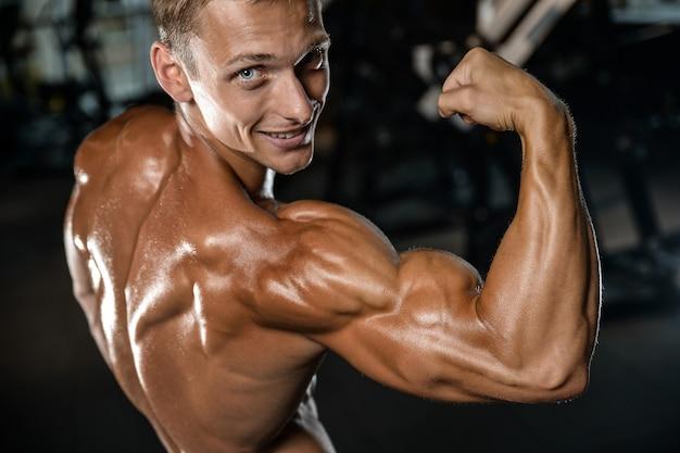 Przystojny model młody człowiek treningu broni w siłowni