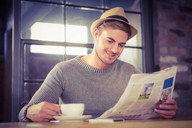 Przystojny modniś ma kawę i czytelniczą gazetę