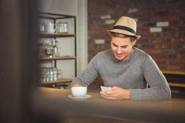 Przystojny modniś ma kawę i używa smartphone