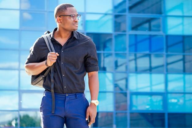 Przystojny modny afroamerykański wykładowca uniwersytetu mężczyzna w okularach w stylowych ubraniach czarna koszula z plecakiem na ramionach stoi na tle niebieskich okien