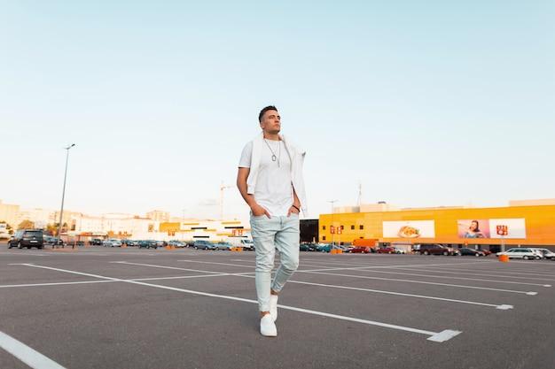 Przystojny modny młody człowiek w modnych niebieskich dżinsach w stylowej białej koszulce w trampkach spaceruje po mieście