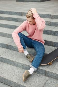 Przystojny modny młody człowiek w różowy sweter i niebieskie dżinsy z deskorolką siedzi na schodach