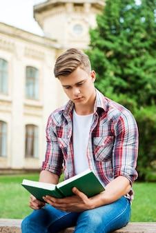 Przystojny mól książkowy. pewny siebie student czytający książkę siedzącą na ławce przed budynkiem uniwersyteckim