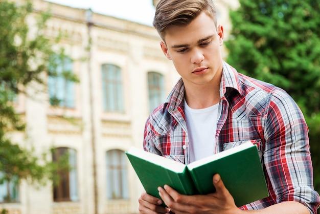Przystojny mól książkowy. przystojny student czytający książkę przed budynkiem uniwersyteckim