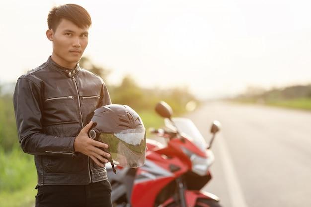 Przystojny motocyklista jest ubranym skórzaną kurtkę i trzyma hełm na drodze