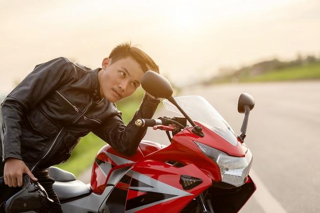 Przystojny motocyklista patrząc w lustro, aby sprawdzić swoją twarz na drodze