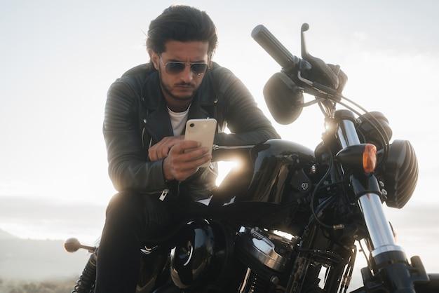 Przystojny motocyklista trzymający smartfon za pomocą aplikacji nawigacyjnej, aby znaleźć najlepszą mapę drogową