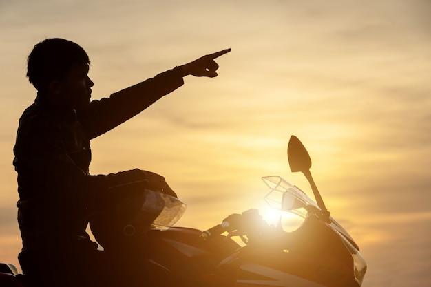 Przystojny motocyklista wskazuje palcem w niebo