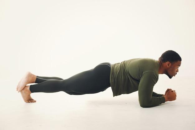 Przystojny murzyn robi joga na białej ścianie