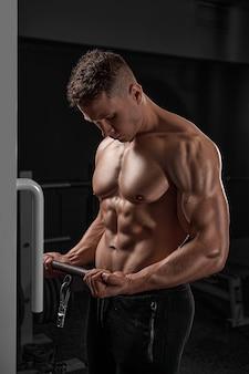 Przystojny muskularny kulturysta fitness wykonujący ciężkie ćwiczenia na biceps na maszynie z kablem