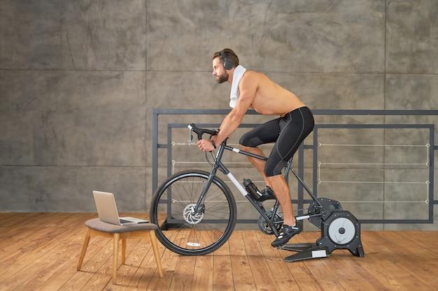 Przystojny muskularny mężczyzna jeżdżący na rowerze treningowym i słuchający muzyki przez bezprzewodowe słuchawki