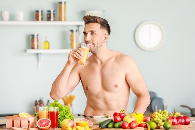 Przystojny, muskularny mężczyzna pije sok w kuchni. koncepcja utraty wagi