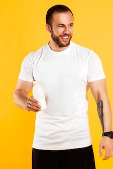 Przystojny muskularny mężczyzna z butelką jogurtu z nasionami chia