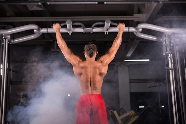 Przystojny, muskularny mężczyzna z doskonałym ciałem robi pull up w siłowni