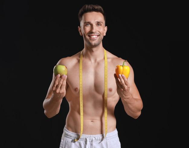 Przystojny muskularny mężczyzna z miarką i jedzeniem na zmrok. koncepcja odchudzania