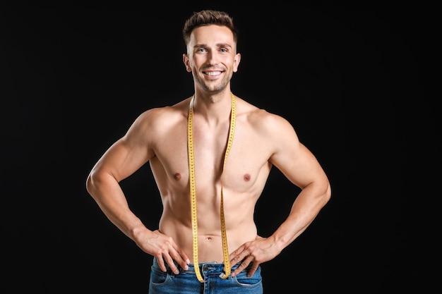 Przystojny muskularny mężczyzna z miarką na ciemnej powierzchni. koncepcja odchudzania