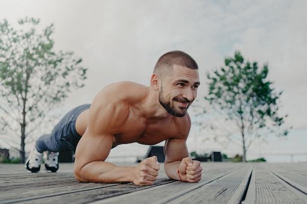 Przystojny, muskularny mężczyzna, z, nagi, tułów, na zewnątrz, robi, fitness, siłownia