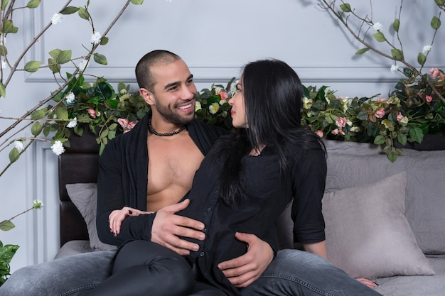 Przystojny muzułmanin siedzi na łóżku ze swoją piękną ciężarną żoną, przytulając jej brzuch i uśmiechając się