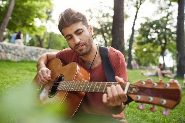 Przystojny muzyk gra na gitarze w parku, siedząc na trawie