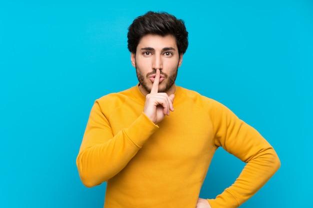 Przystojny nad odosobnioną błękit ścianą pokazuje znaka cisza gesta kładzenia palec w usta