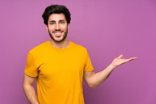 Przystojny nad odosobnioną purpury ściany mienia copyspace wyimaginowanym na dłoni, aby wstawić reklamę